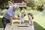 Grandfather and grandchildren building up a birdhouse - RBF004753