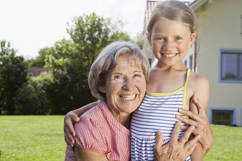 Portrait of happy grandmother and granddaughter in garden - RBF004798