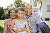 Portrait of happy grandparents with granddaughter in garden - RBF004801