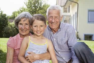 Portrait of happy grandparents with granddaughter in garden - RBF004801