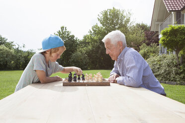 Grandfather and grandson playing chess in garden - RBF004804