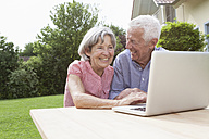 Happy senior couple using laptop in garden - RBF004810