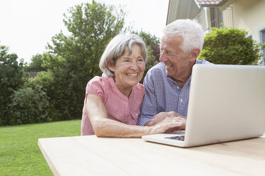 Happy senior couple using laptop in garden - RBF004810