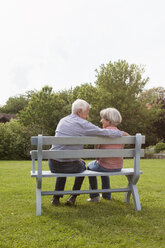 Happy senior couple sitting on bench in garden - RBF004816