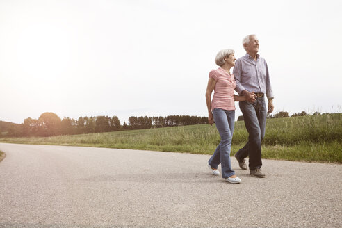 Smiling senior couple walking on country road - RBF004819