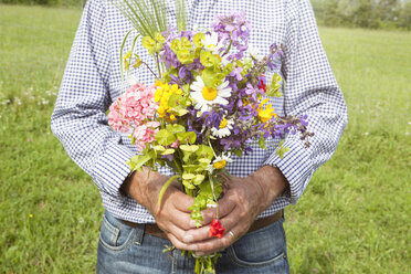 Senior man holding bunch of flowers outdoors - RBF004828