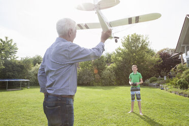 Grandfather and grandson with model airplane in garden - RBF004831