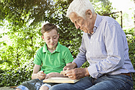 Grandfather and grandson carving together - RBF004834