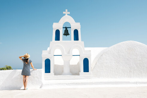 Greece, Santorini, Oia, back view of woman standing next to bell tower looking to the sea - GEMF000931
