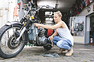 Young woman cleaning motorbike - MADF001036