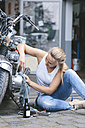 Young woman cleaning motorbike - MADF001042