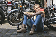 Young woman with beer bottle sitting next to motorbike - MADF001045