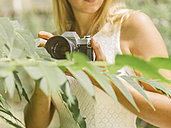 Young woman behind plant holding camera - MADF001051