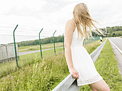 Young woman in white dress standing at the roadside - MADF001054