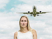 Flying plane behind young woman in white dress - MADF001057