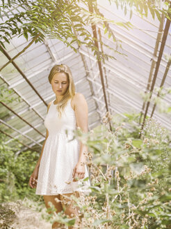 Blond young woman in white dress standing in greenhouse - MADF001060