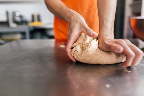 Woman's hand kneading pizza dough, close-up - MGOF002073