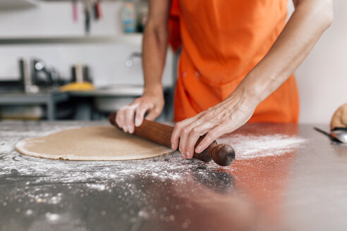 Hands of woman rolling out pizza dough, close-up - MGOF002076