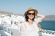 Greece, Santorini, Oia, portrait of smiling woman wearing sunglasses and straw hat - GEMF000933