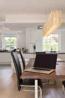 Modern dining area with open plan kitchen in the background - SHKF000631
