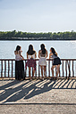 Back view of four friends standing at sunlight in front of water - ABZF000869