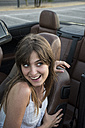 Smiling young woman sitting in convertible pulling funny faces - ABZF000884
