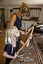 Mother and daughter in workshop working on Stone-Age spear-thrower - TCF005023