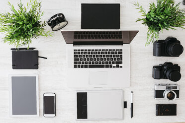 Desk of photographer with laptop, cameras, tablet and graphics tablet - JRFF000774