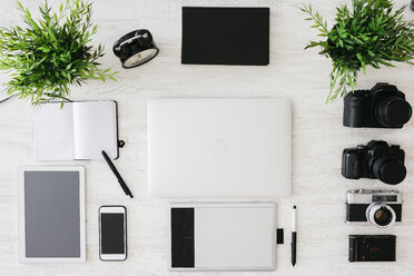 Desk of photographer with notebook, laptop, cameras, tablet and graphics tablet - JRFF000777