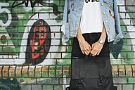 Young man in jeans jacket holding black bag - JUBF000172