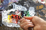 Hand holding used spatula in front of artist's palette - JTF000766