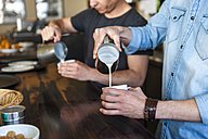Two men preparing coffee with milk in a cafe - DIGF000795