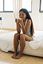 Young woman sitting on bed drinking coffee - EBSF001550