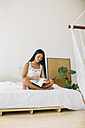 Young woman sitting on bed reading book - EBSF001556