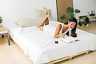 Young woman lying in bed reading book - EBSF001559