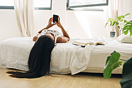 Young woman lying in bed using cell phone - EBSF001565