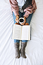 Woman with cup of coffee and book relaxing on bed, partial view - EBSF001625