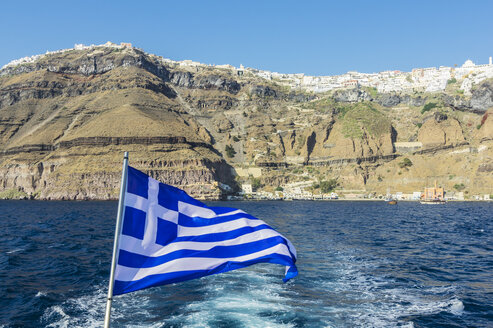 Greece, Santorini, Greek flag with Fira in the background seen from from Caldera - THAF001715