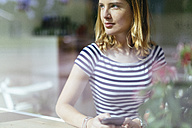 Young woman in a coffee shop looking through window - GIOF001315