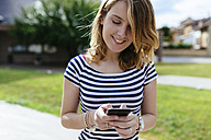 Smiling young woman text messaging - GIOF001324