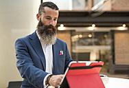 Bearded man looking tablet at terrace - JASF001023