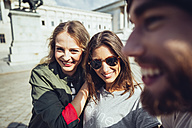 Austria, Vienna, three friends having fun in front of the parliament building - AIF000354