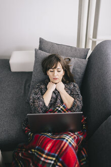 Young woman covered with a blanket lyng on couch with laptop - LCUF000026