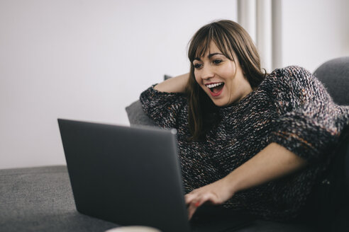 Amazed woman lying on the couch looking at laptop - LCUF000029
