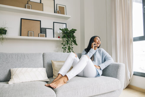 Laughing young woman sitting on couch at home telephoning with cell phone - EBSF001642