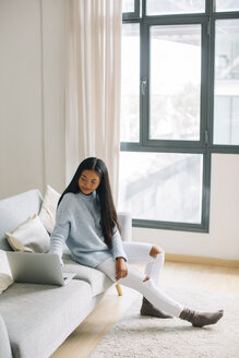Smiling young woman sitting on couch at home using laptop - EBSF001648