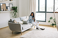 Young woman with smartphone sitting on couch at home looking at laptop - EBSF001651