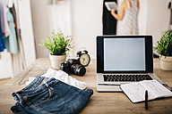 Laptop, clothes and sketchbook on desk with woman in background - JRFF000806