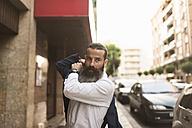 Bearded man putting on his jacket on pavement - JASF001024