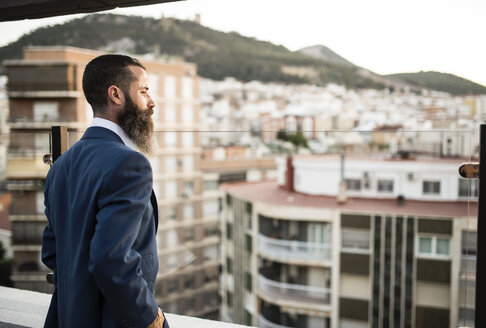 Bearded businessman standing on roof terrace looking at distance - JASF001027